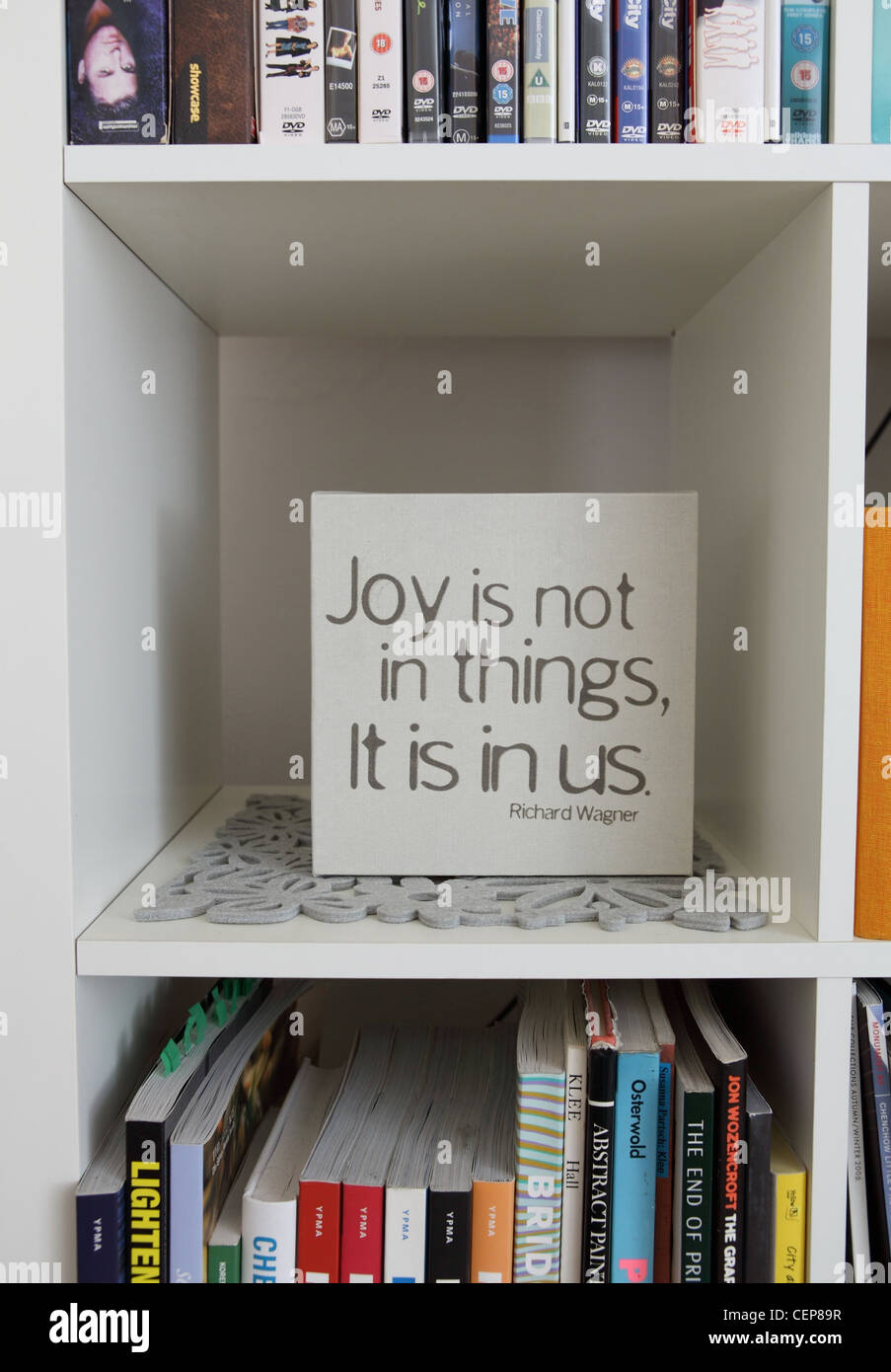 Apartment in Sydney Joy is not in things, it is in us sign on squared book shelf - Stock Image