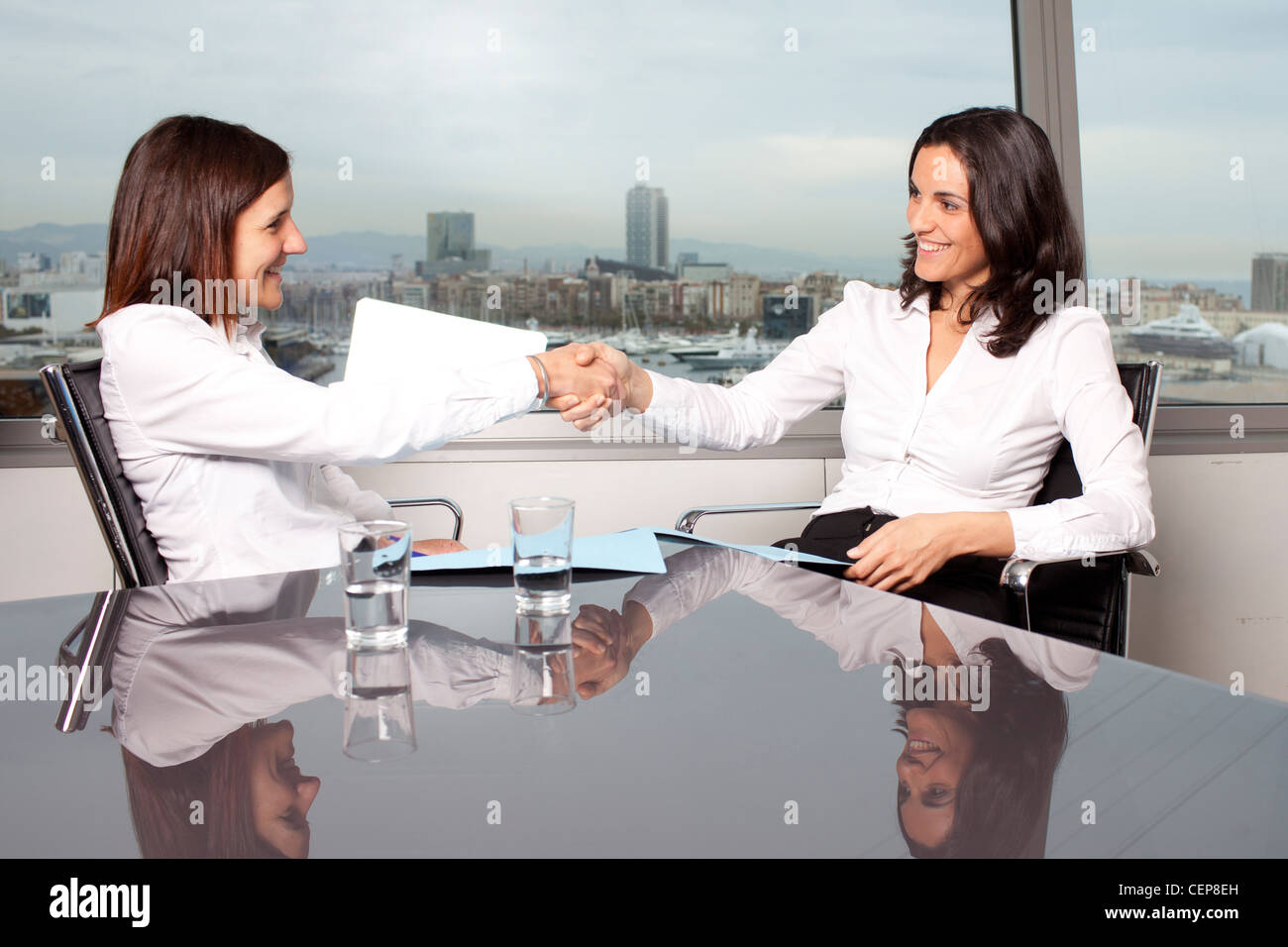 Female boss shake hands with successful candidate - Stock Image