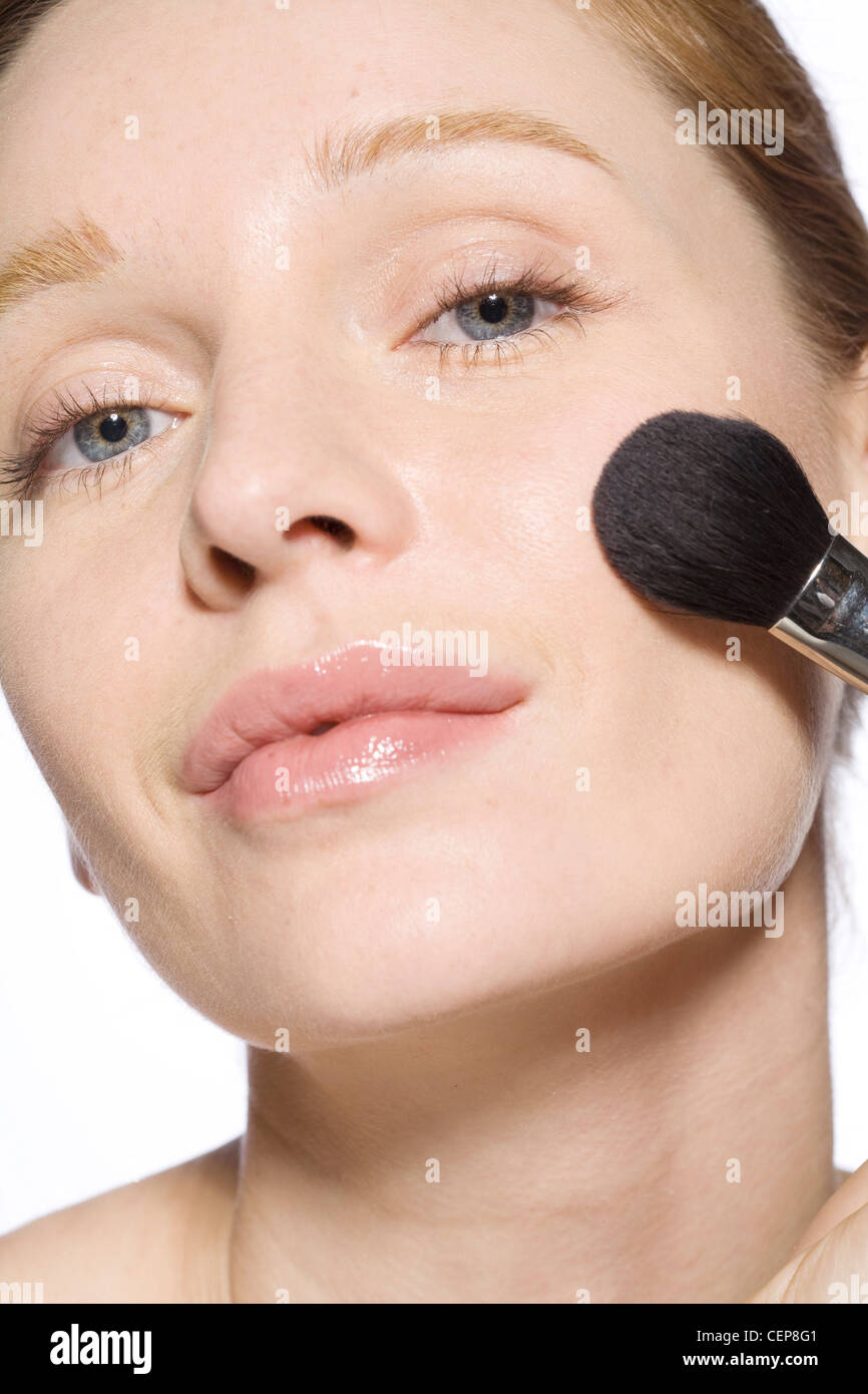 Female with fair hair off her face, wearing minimal make up, applying blusher to her cheek with a make up brush - Stock Image