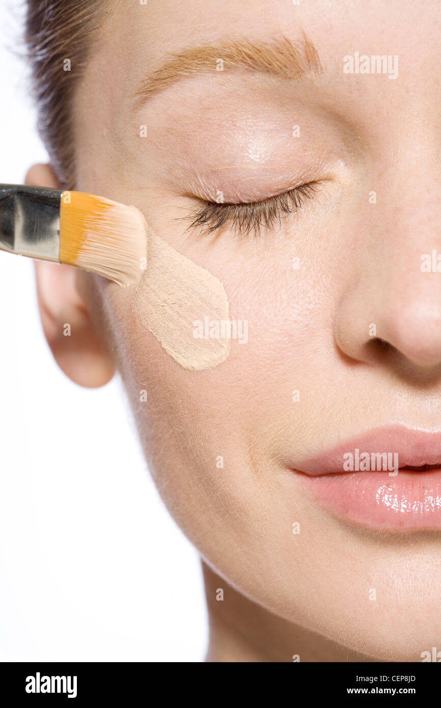 Female with fair hair off her face, wearing minimal make up, applying highlighter to her cheek with a make up brush - Stock Image