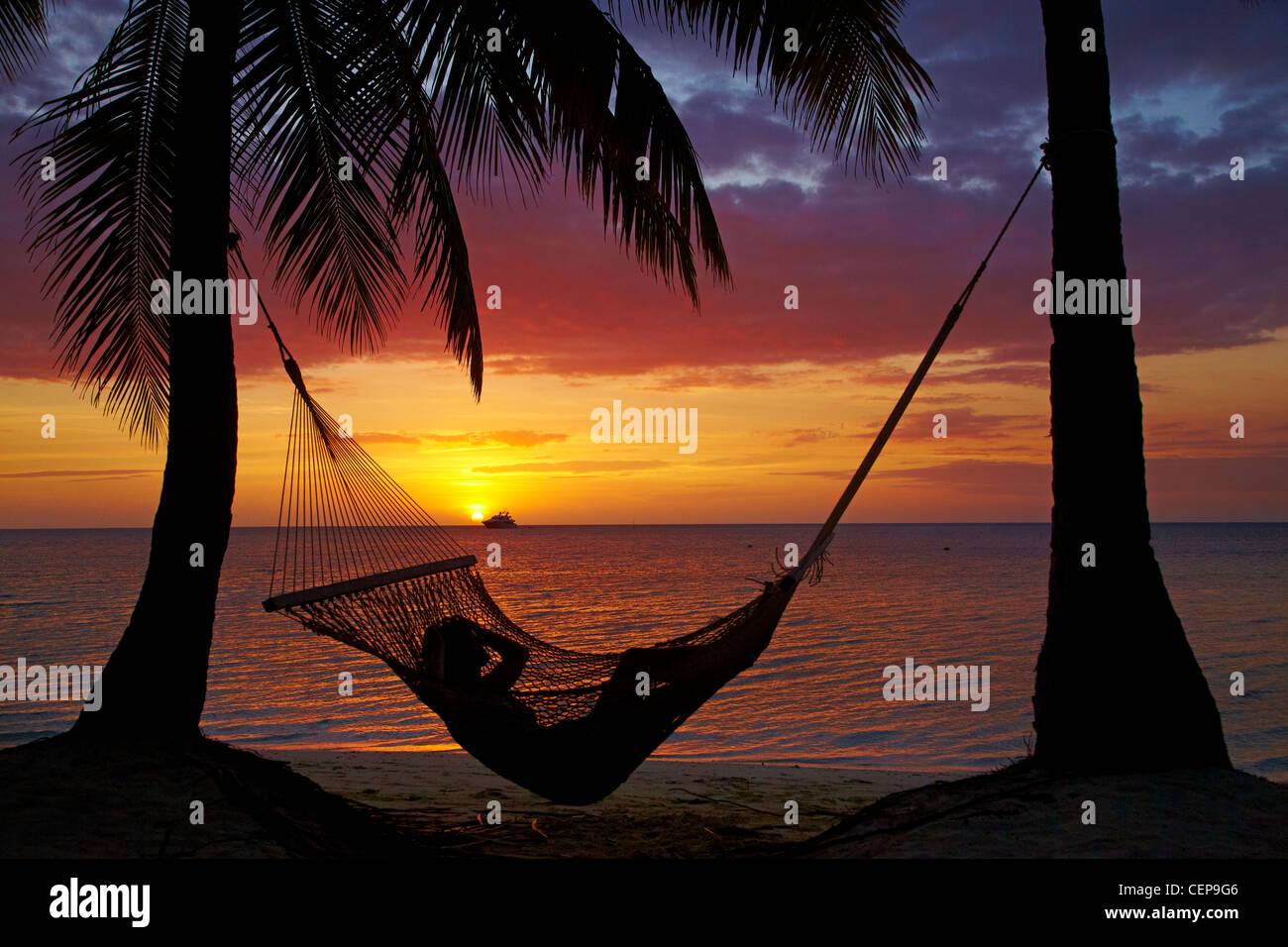 Hammock and sunset, Plantation Island Resort, Malolo Lailai Island, Mamanuca Islands, Fiji, South Pacific - Stock Image