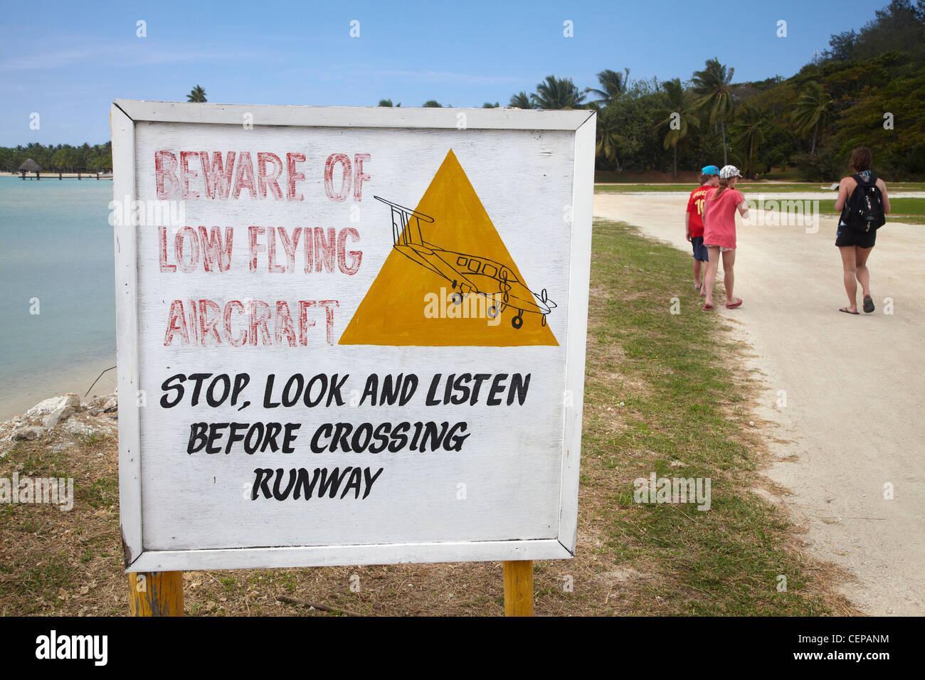 Warning sign beside footpath across runway, between resorts, Malolo Lailai Island, Mamanuca Islands, Fiji, South - Stock Image