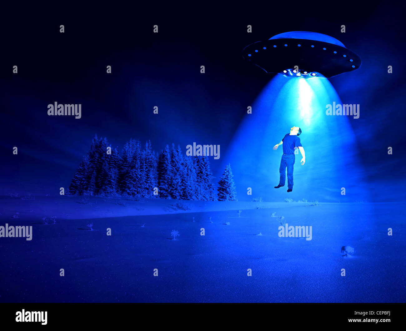 Man being abducted by aliens on a winter night. Stock Photo