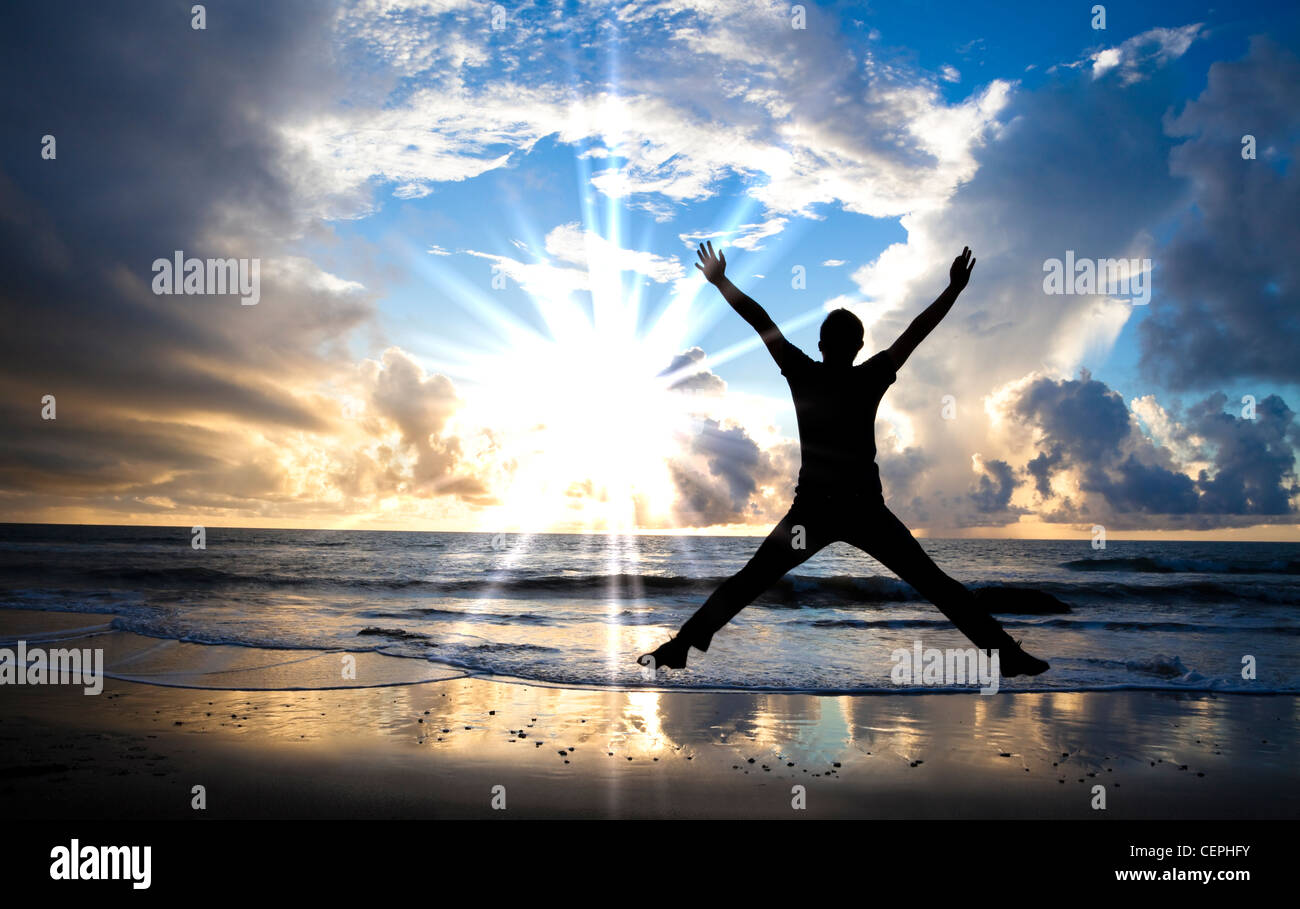 happy man jumping on the beach with beautiful sunrise - Stock Image