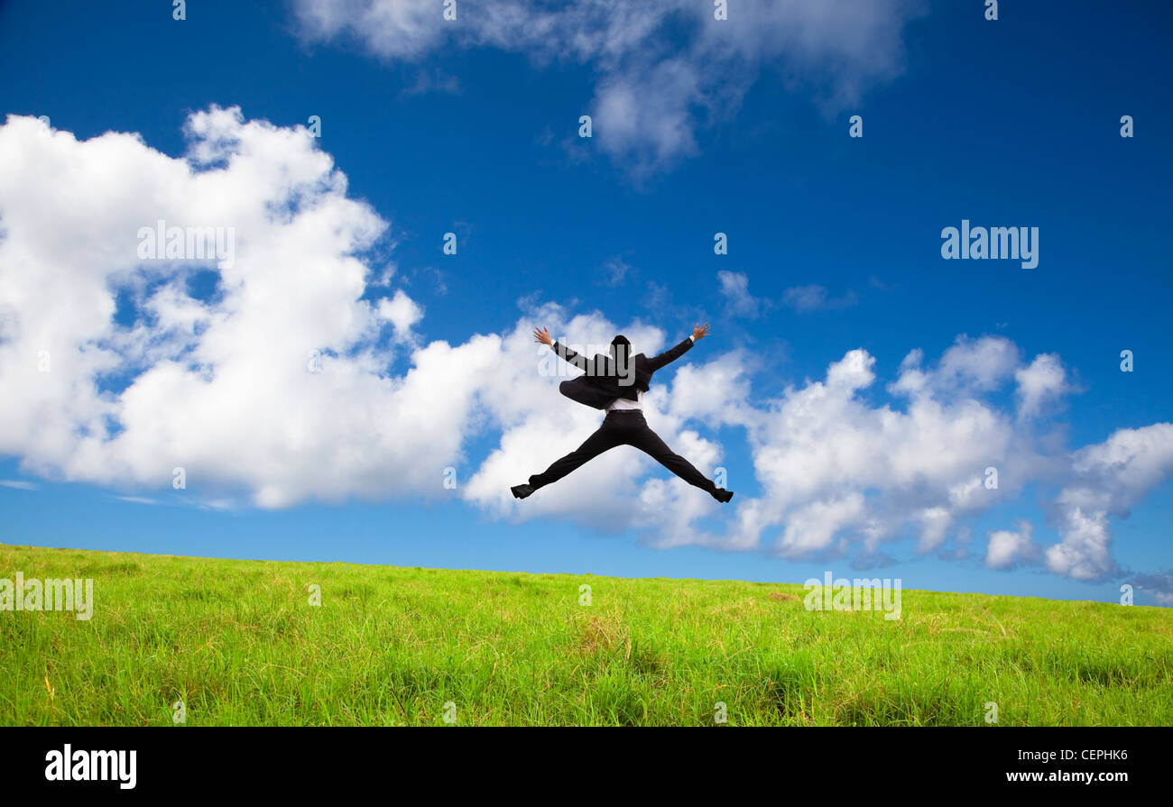 happy and successful Businessman jumping on a green meadow - Stock Image