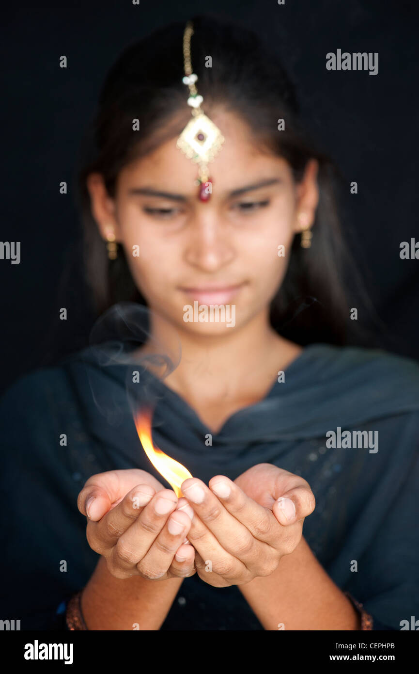 Indian hindu teenage girl holding a camphor flame. India - Stock Image