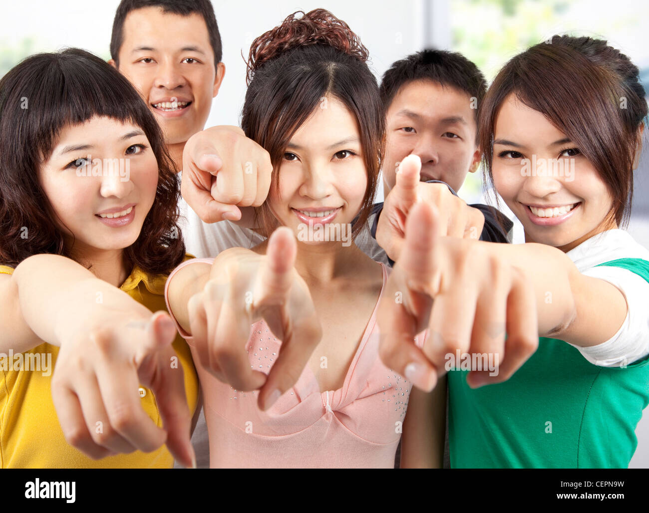 Portrait of a smiling asian students pointing at you - Stock Image