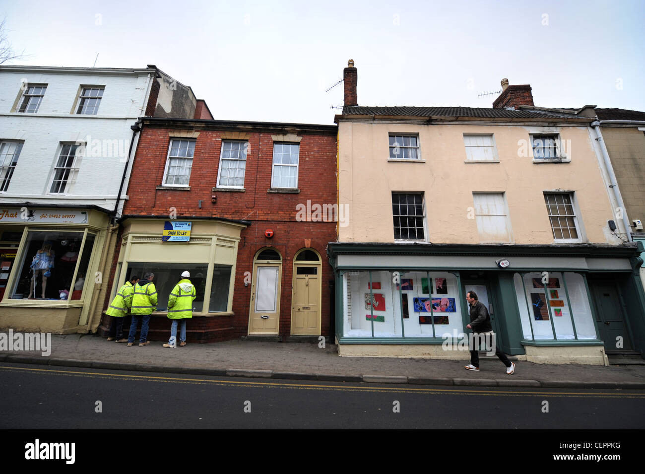 Construction workers look into an unoccupied shop in temporary use as an art gallery in Dursley, Gloucestershire, - Stock Image