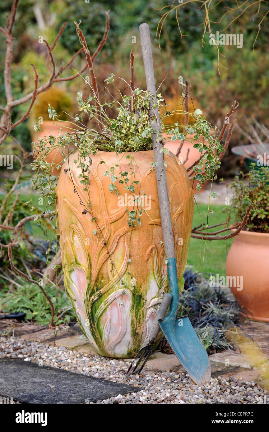 A garden urn and traditional spade with winter plants Powys UK - Stock Image