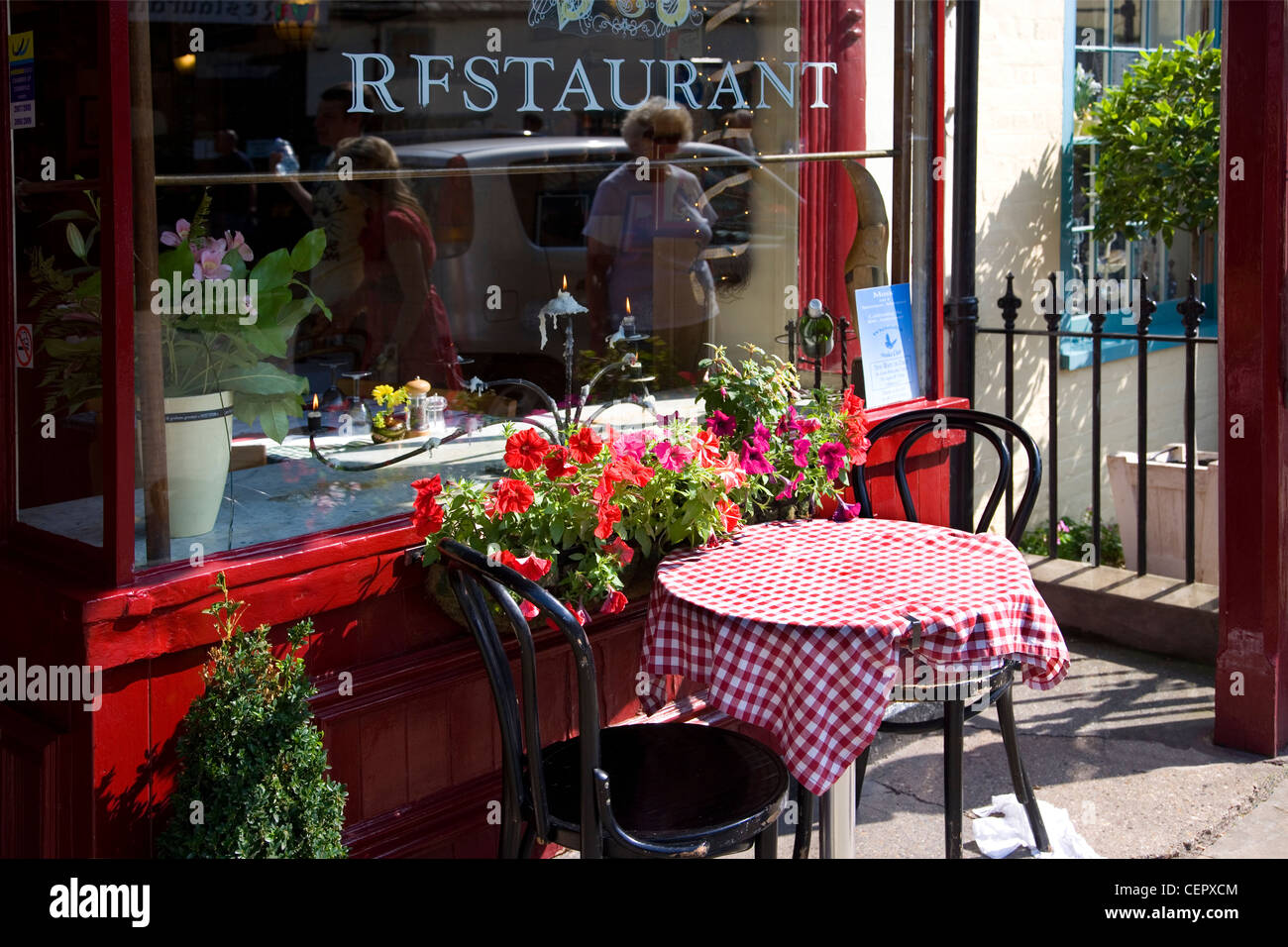 A table with a red and white chequered table cloth outside a small restaurant in Whitstable town centre. - Stock Image