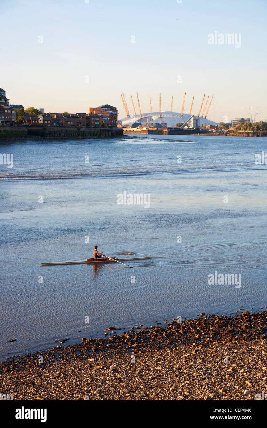 A rower training on the River Thames with the O2 in the background. - Stock Image
