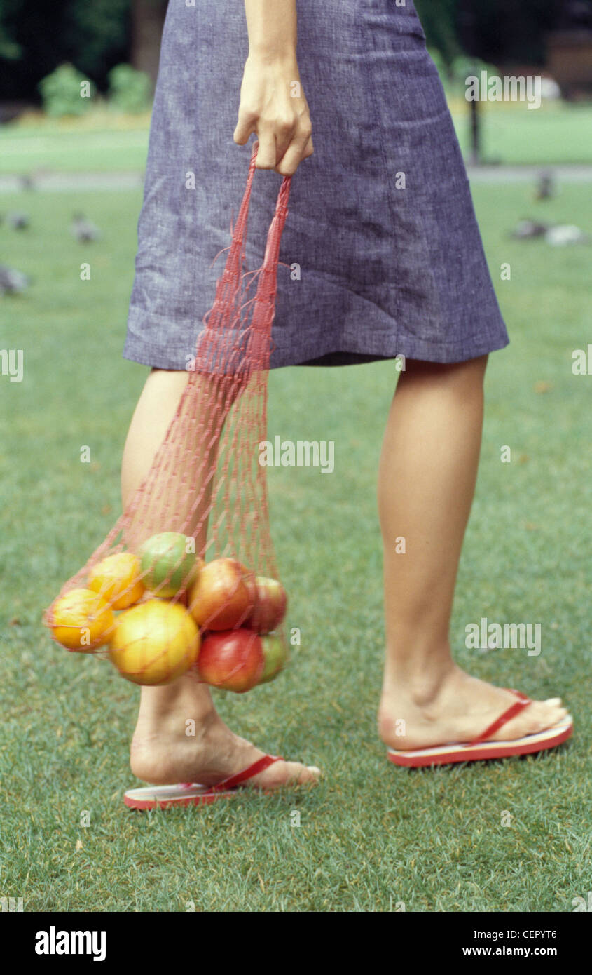 d9e3f215f612a Cropped female wearing denim skirt and red flip flops walking in park  holding red string bag of mixed fruit