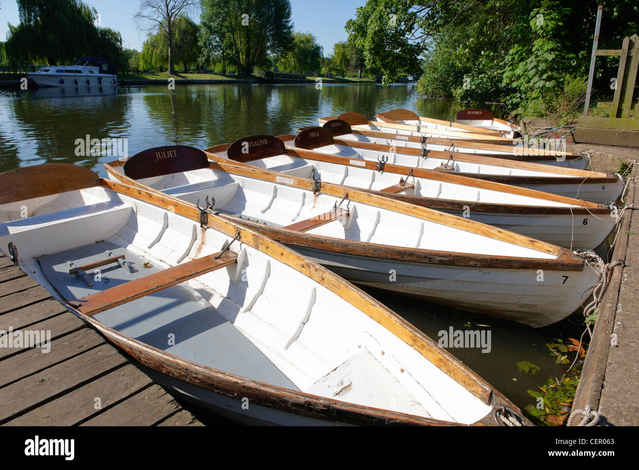 A line of rowing boats for hire, each named after a Shakespearean character, moored by the river bank of the River - Stock Image
