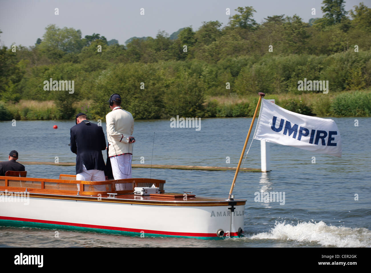 The umpire's boat following a race up the course at the annual Henley Royal Regatta. - Stock Image