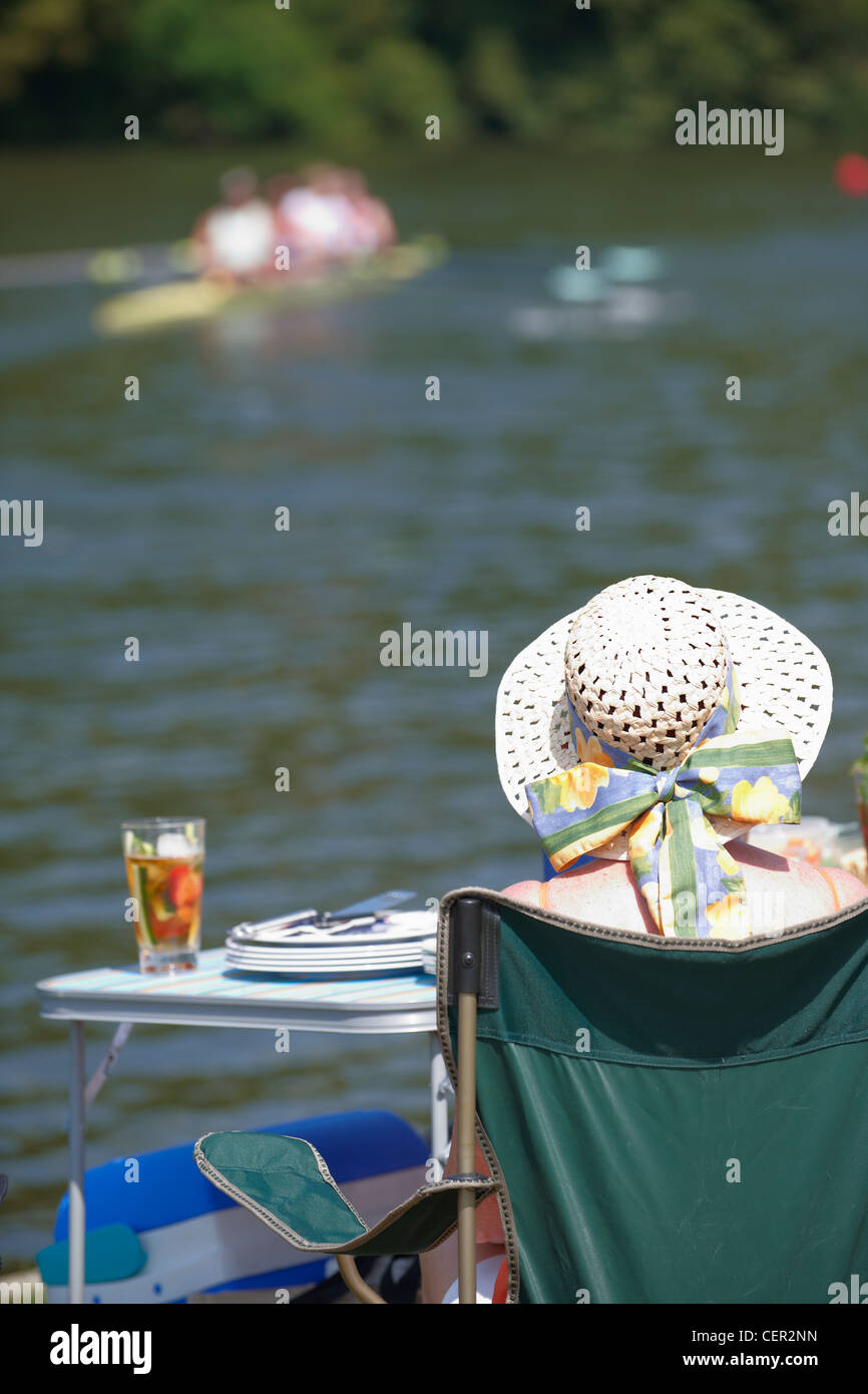 A woman relaxing on the river bank with a glass of Pimms watching a race at the annual Henley Royal Regatta. - Stock Image