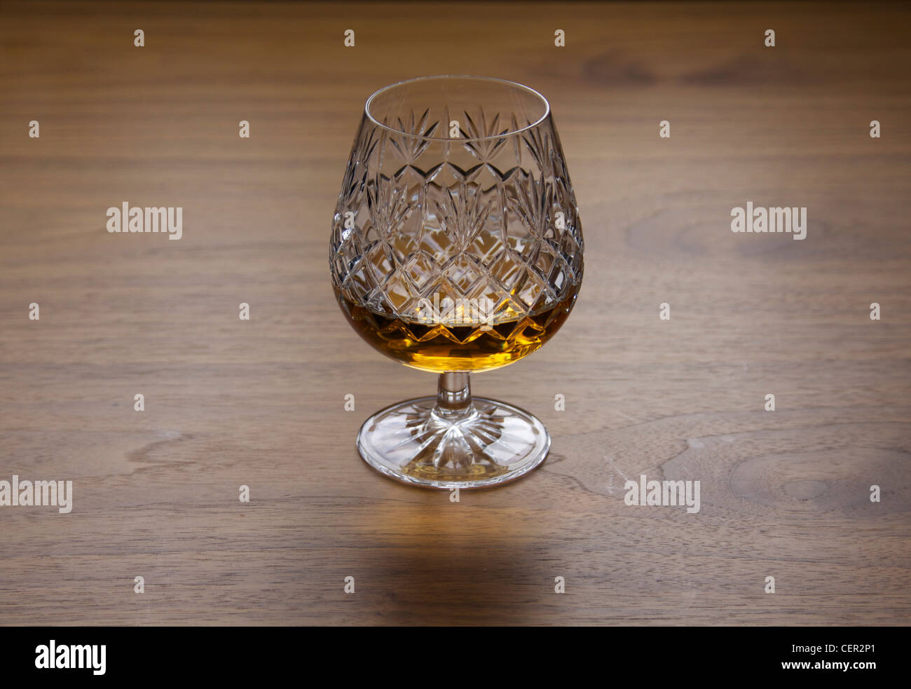 Traditional brandy glass made from cut crystal with brandy or whiskey whisky with diamond detail pattern on wooden - Stock Image