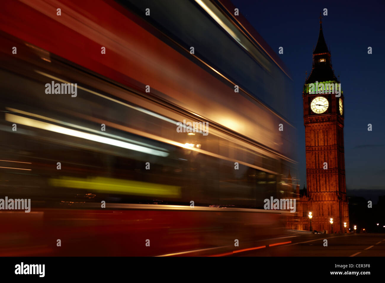 A red double decker bus passing Big Ben at night in Westminster. - Stock Image