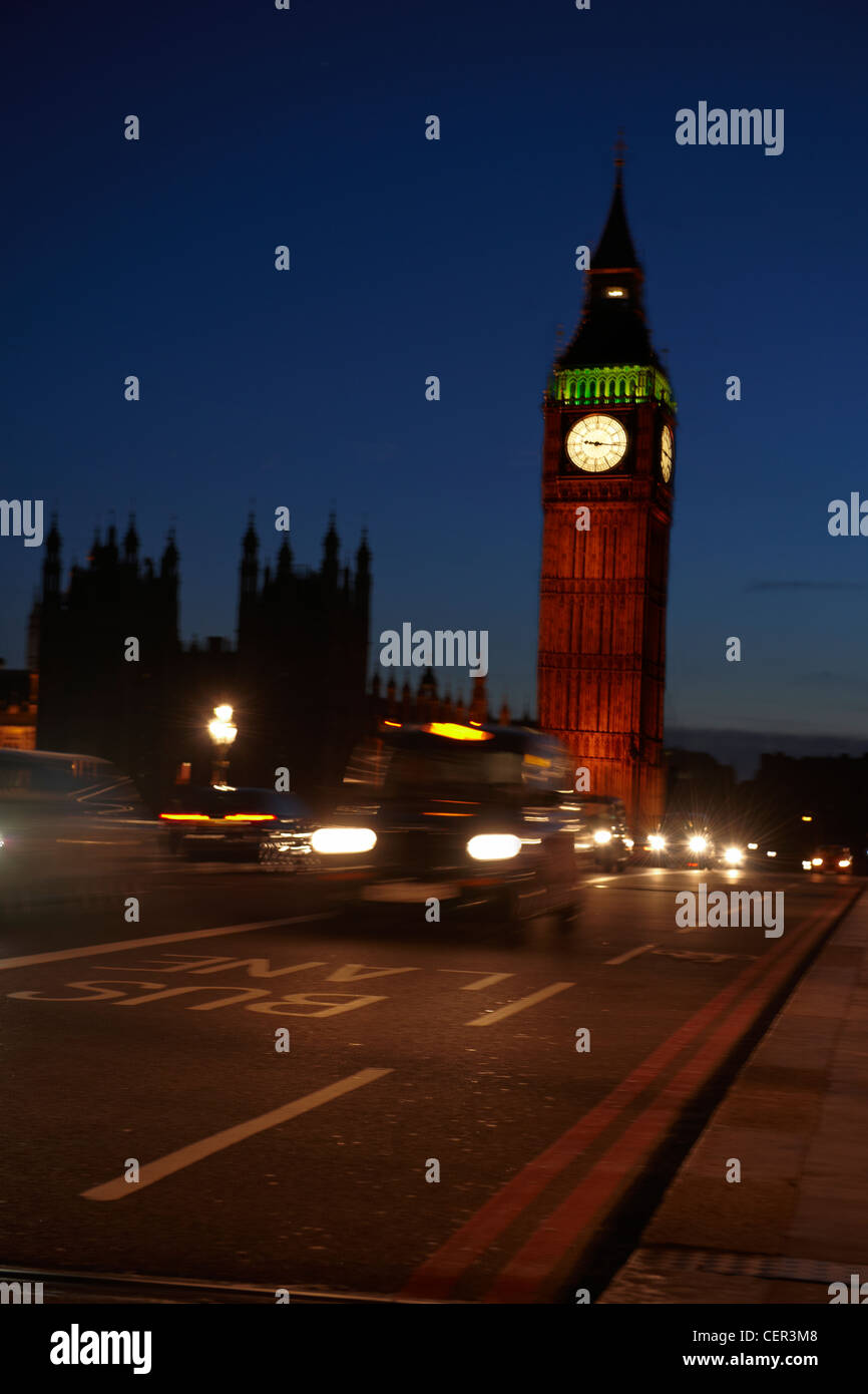 Big Ben at night with a taxi passing over Westminster Bridge. - Stock Image