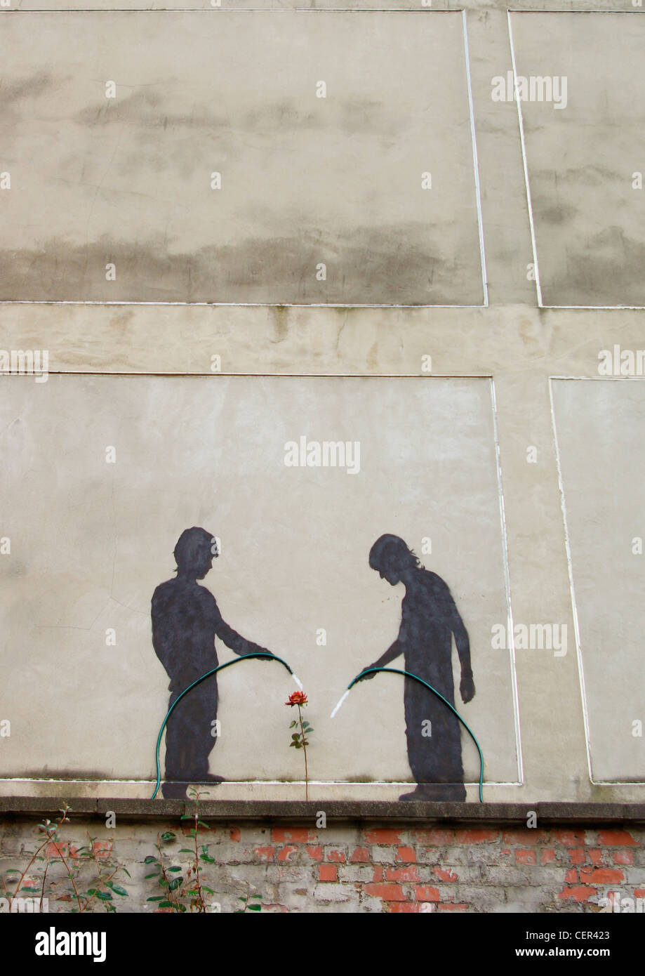 Urban art of two children watering a flower. - Stock Image
