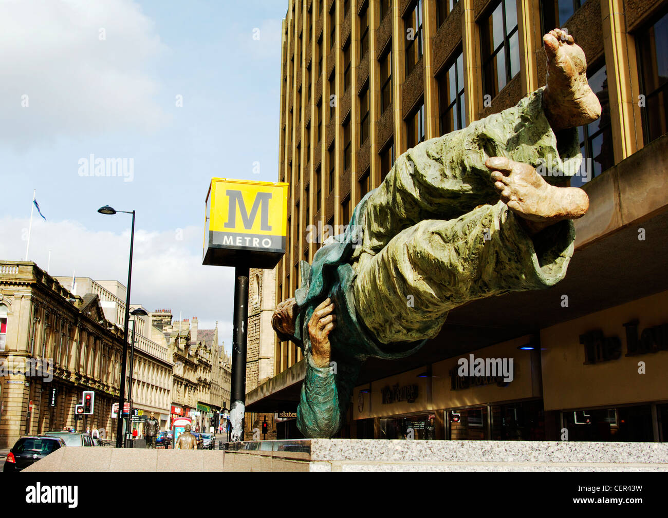 A modern bronze sculpture of a man lying sideways supported on one elbow outside a Metro station. - Stock Image