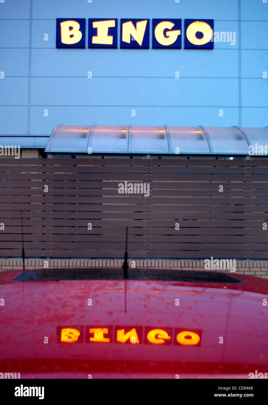 A lit up bingo sign reflected on a car roof. Stock Photo