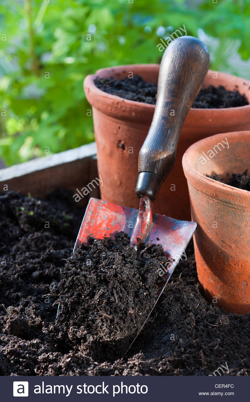 trowl loamy soil compost garden hand tool practical job potting shed pots terra cotta - Stock Image