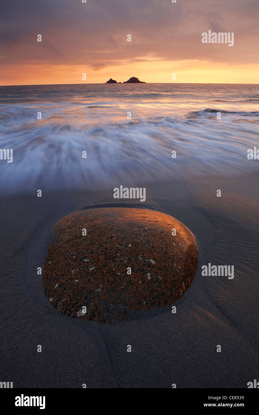 The tide rolling onto Porth Nanven beach towards a large ovoid rock in the foreground at sunset. - Stock Image