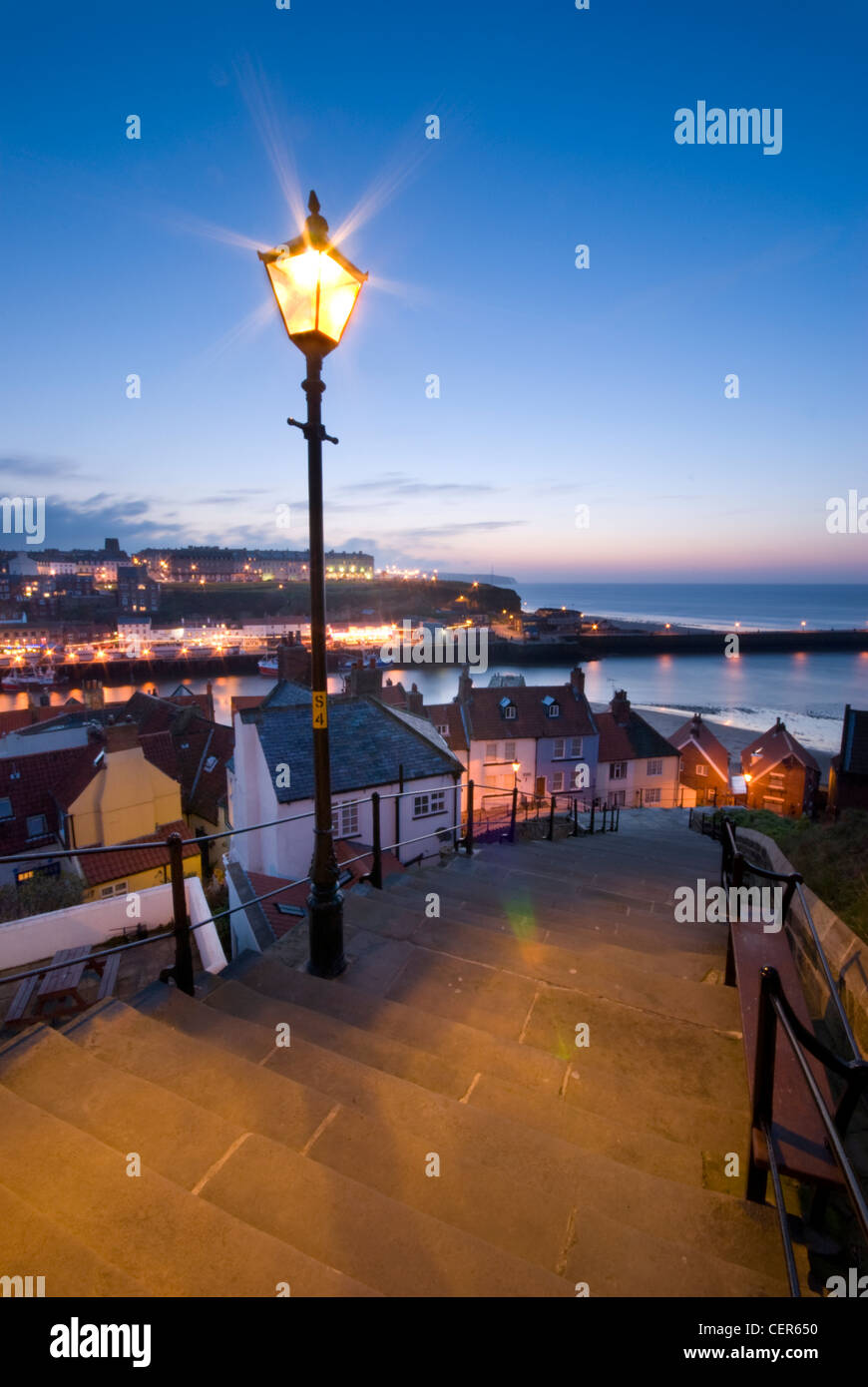 A traditional street light illuminates the 199 steps leading down towards the old town of Whitby. - Stock Image