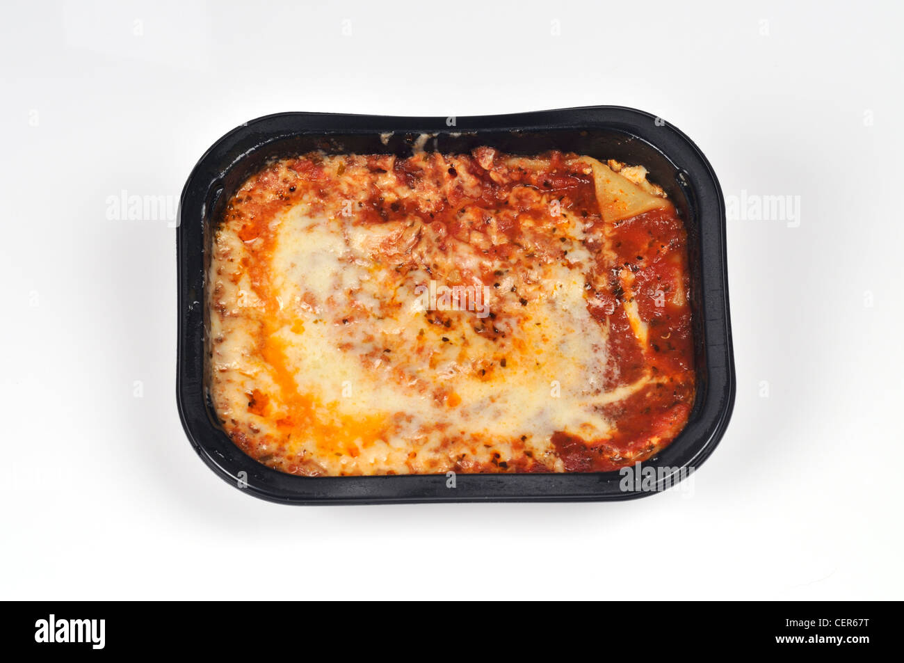 Cooked cheese lasagna ready meal in black plastic tray on white background cutout. - Stock Image