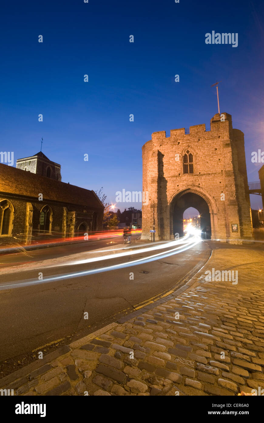 The Westgate Tower in Canterbury lit up at night with trials of light from passing traffic. - Stock Image