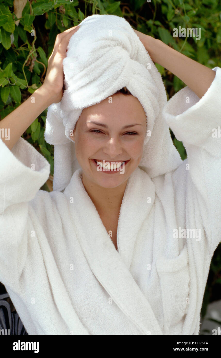 Female hair wrapped up in white towel, wearing white towelling Stock ...