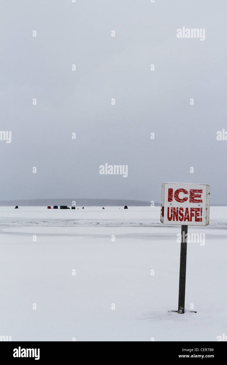 A sign on a frozen lake that reads 'ice unsafe'. - Stock Image