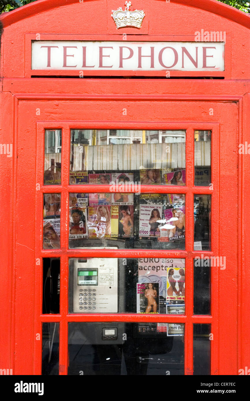 A telephone kiosk with call cards left by prostitutes. These cards, many featuring photographs which one can assume - Stock Image