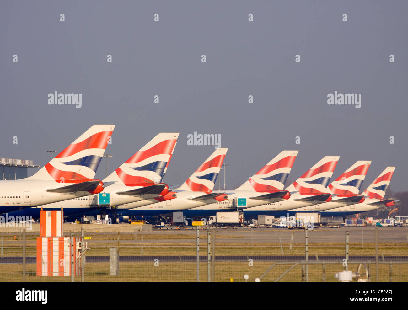 A row of tail fins from British Airways Jumbo jets outside a terminal at Heathrow airport. - Stock Image