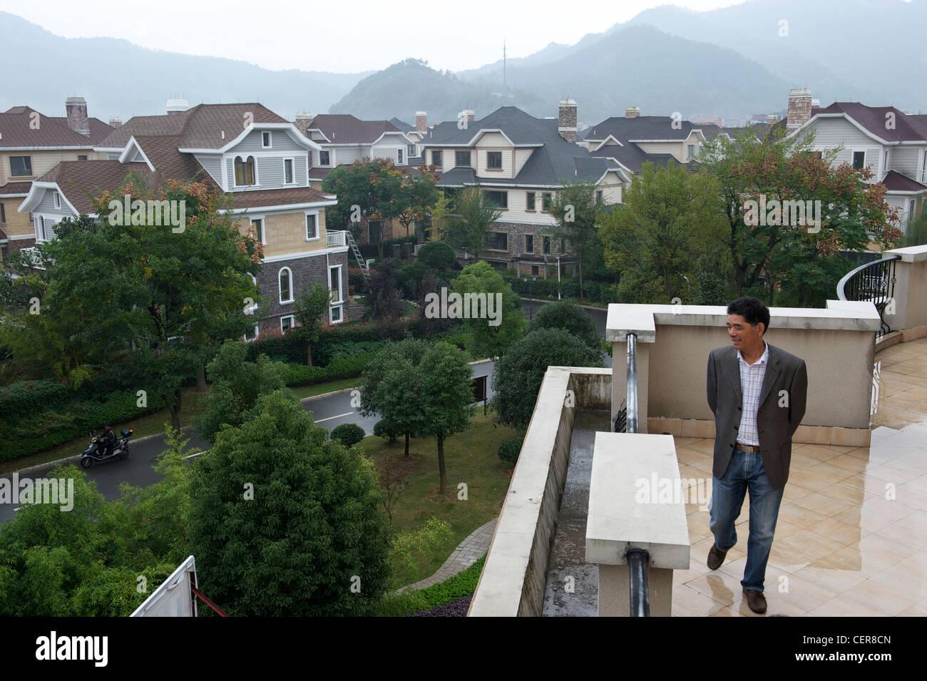 Hu Jishen,Chairman of  Xingyue Group, looks at luxurious villas developed by Xingyue in Yongkang, Zhejiang, - Stock Image