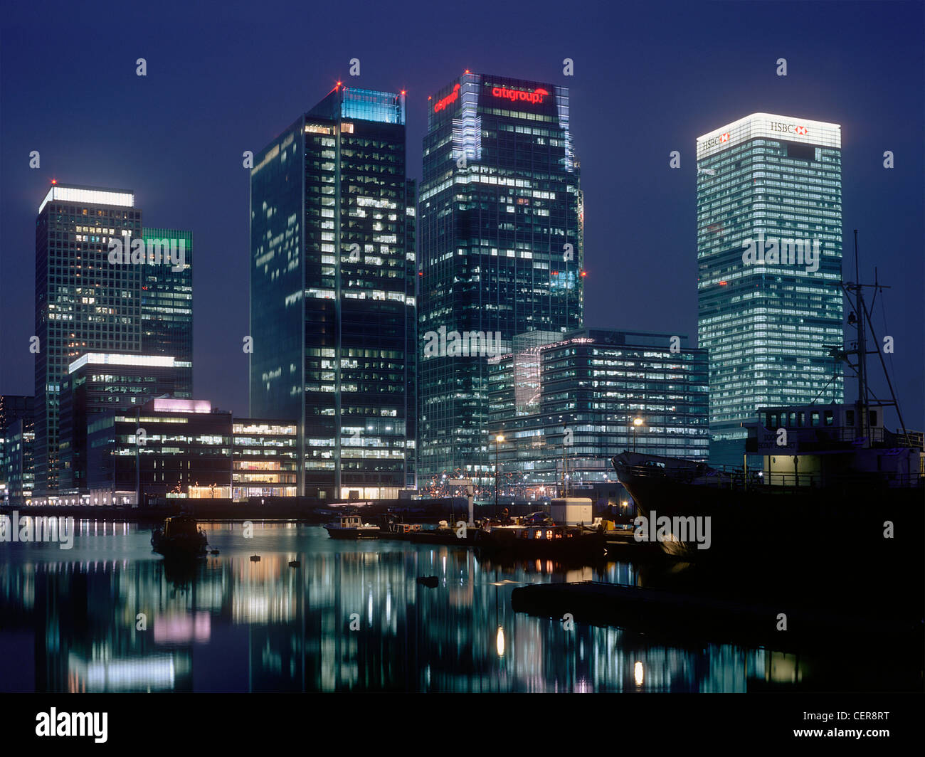 Office blocks reflected in the waters of the West India Docks at night. Canary Wharf is home to three of the tallest - Stock Image