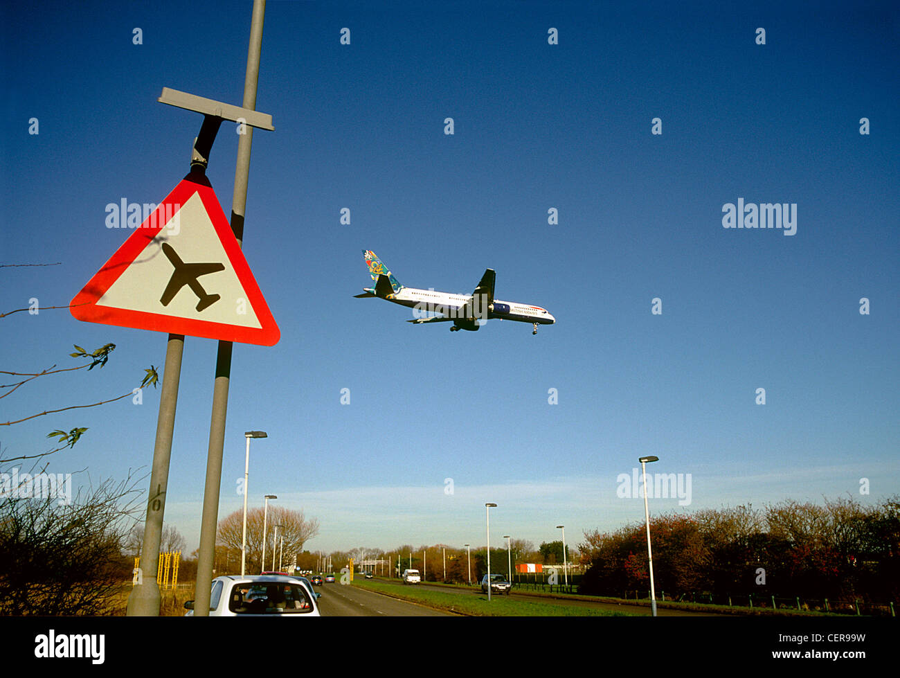 An aircraft coming in to land at Heathrow airport passing above a low flying plane sign by the roadside. - Stock Image