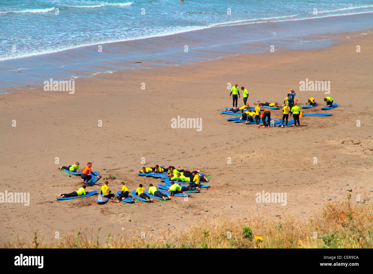 Two groups of holiday makers on a sandy beach learning to surf at Widemouth Bay on the north Cornwall coast near - Stock Image