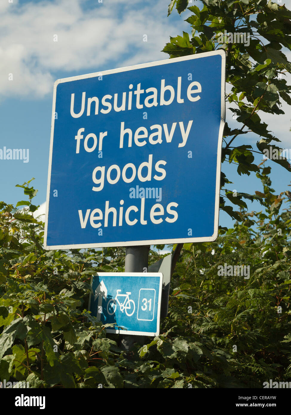 WARNING ROAD SIGN ON COUNTRY ROAD UNSUITABLE FOR TRUCKS WITH BICYCLE ROUTE MARKER IN HEDGE - Stock Image