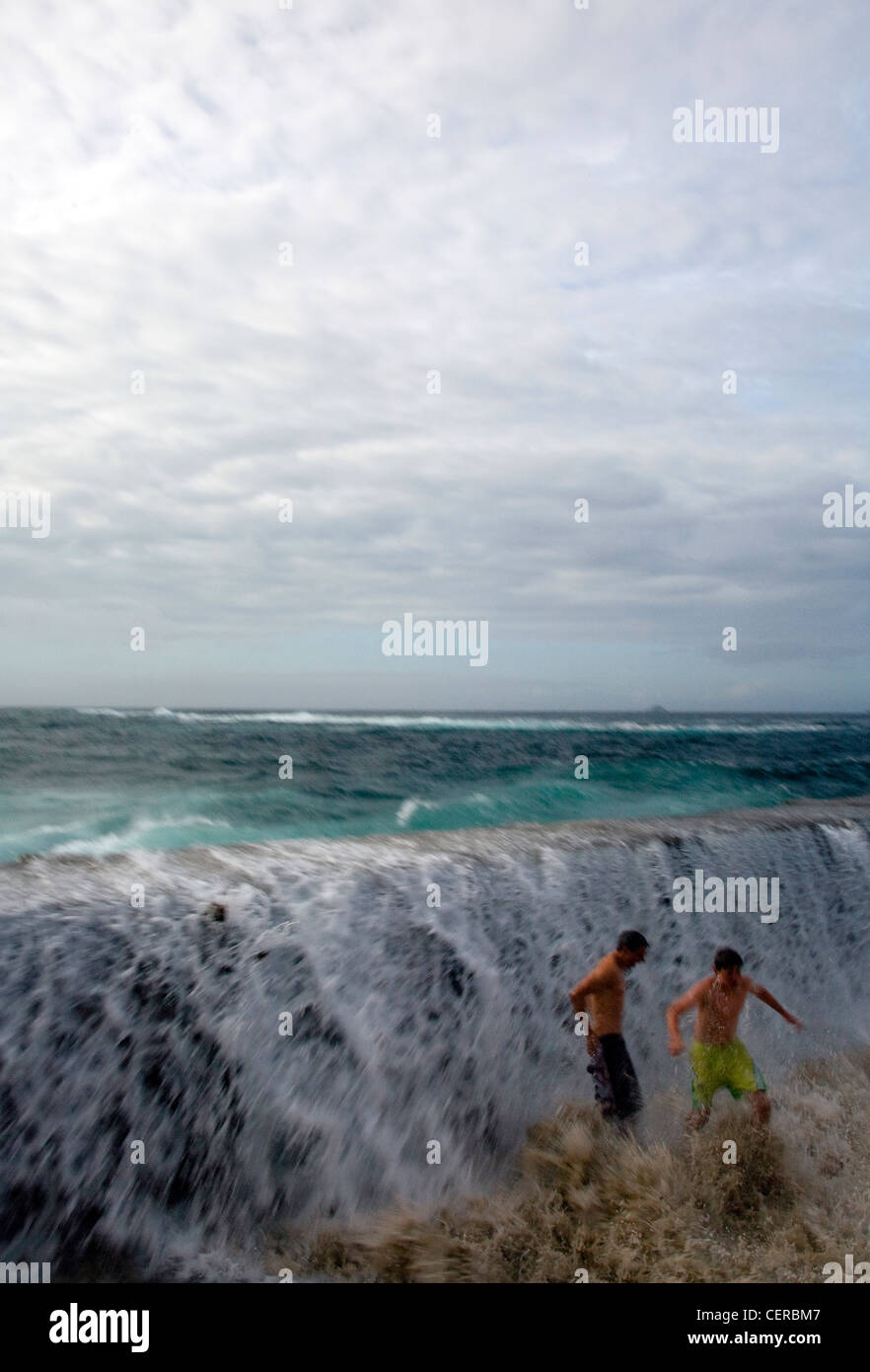 Waves crashing over the breakwater in a storm, soak two visitors, who are in danger of having their feet swept from - Stock Image