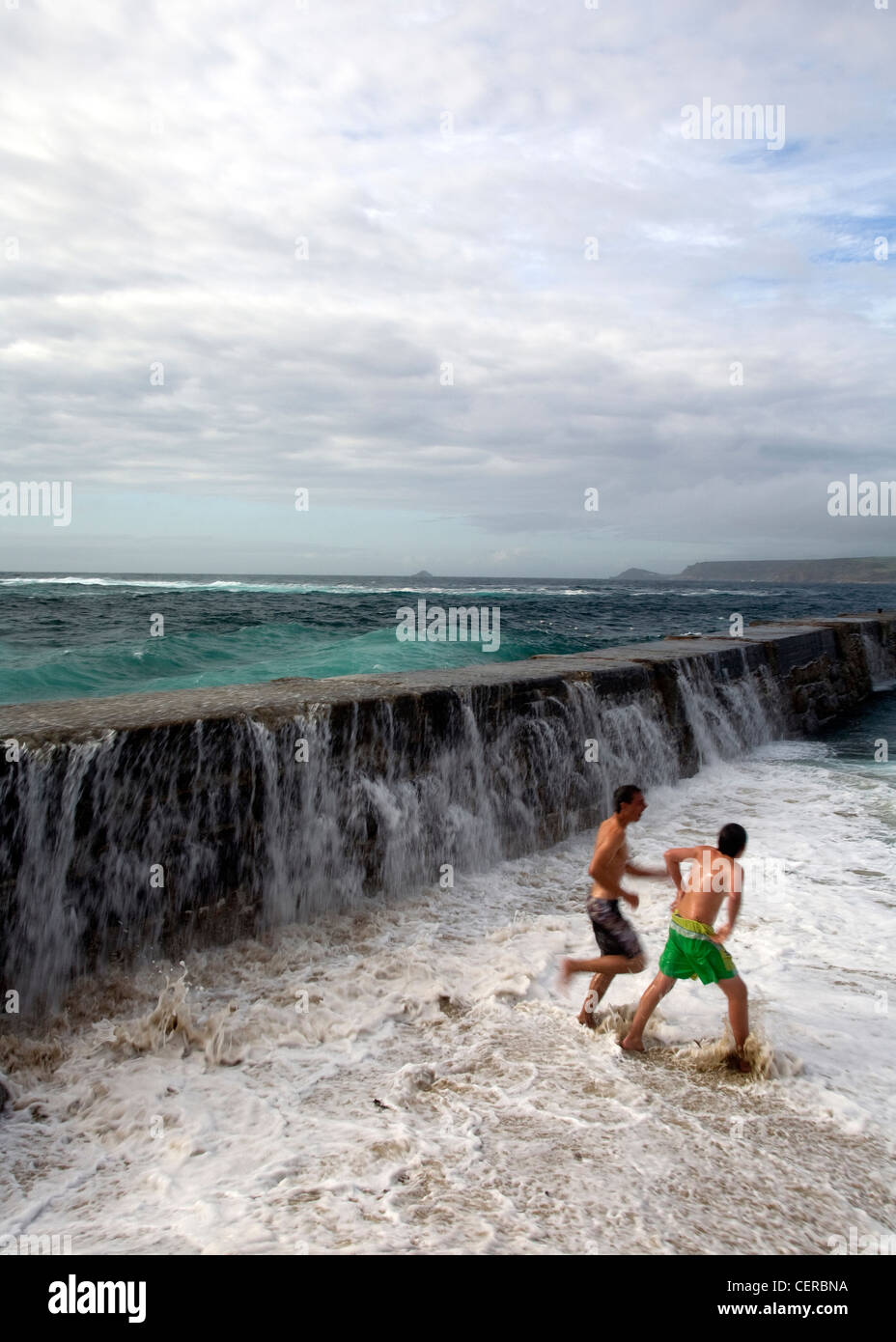 Running away. Escaping the stormy  waves crashing over the breakwater, drenching visitors, with violent explosions - Stock Image