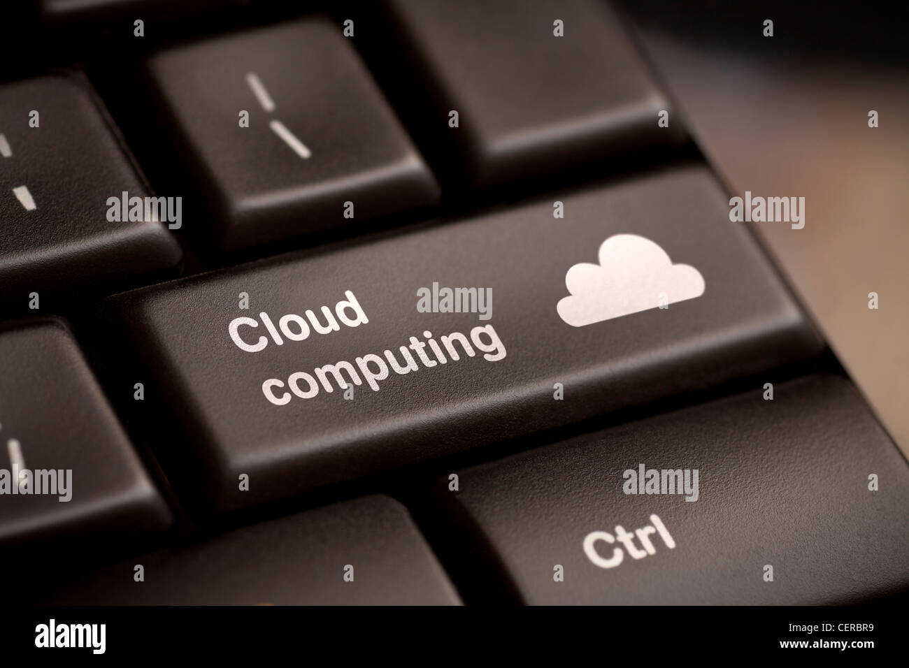 Cloud computing concept showing cloud icon on computer key. - Stock Image