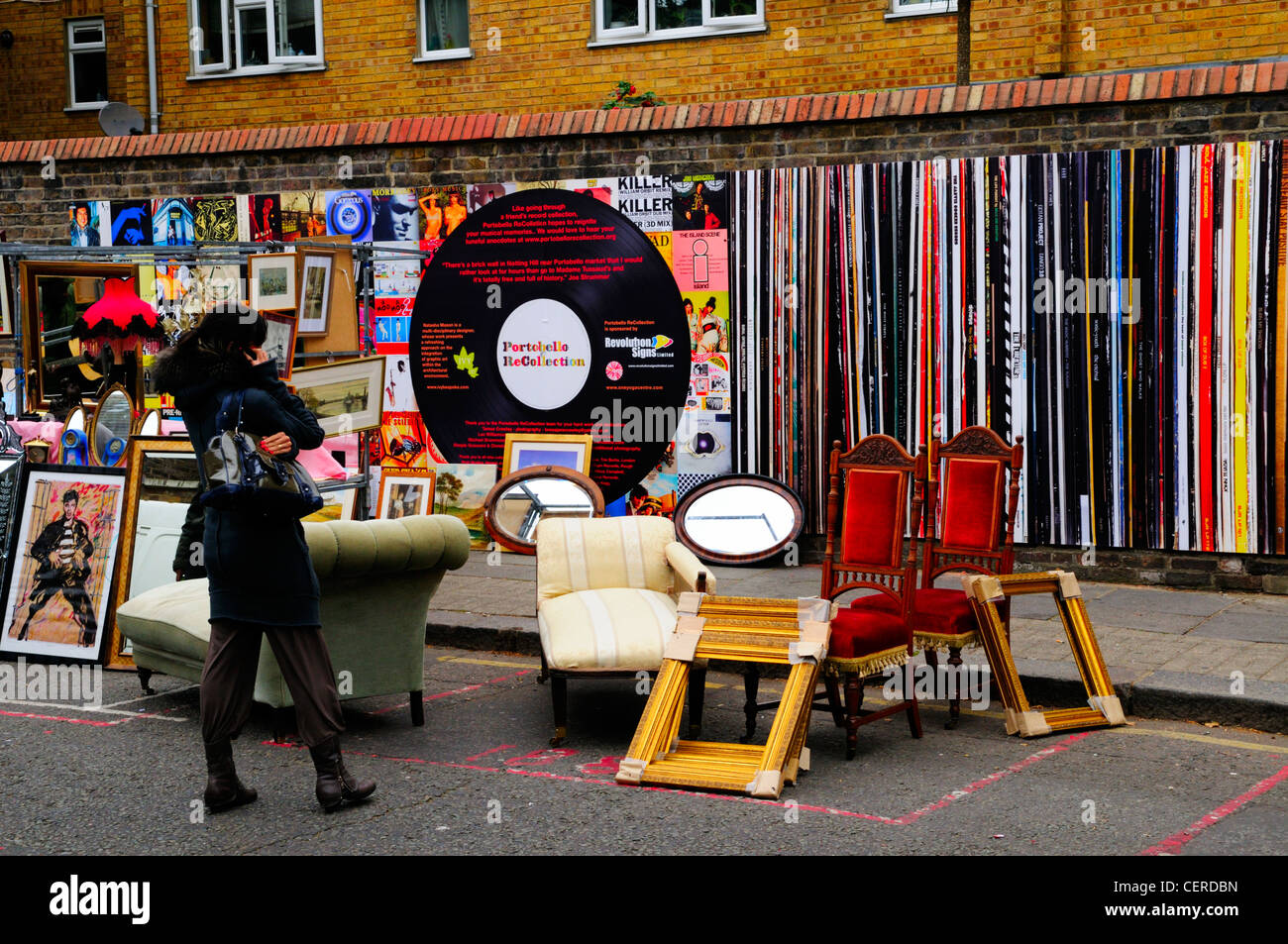 Furniture and picture frames for sale in the street in front of Portobello ReCollection, a wall decorated as classic - Stock Image