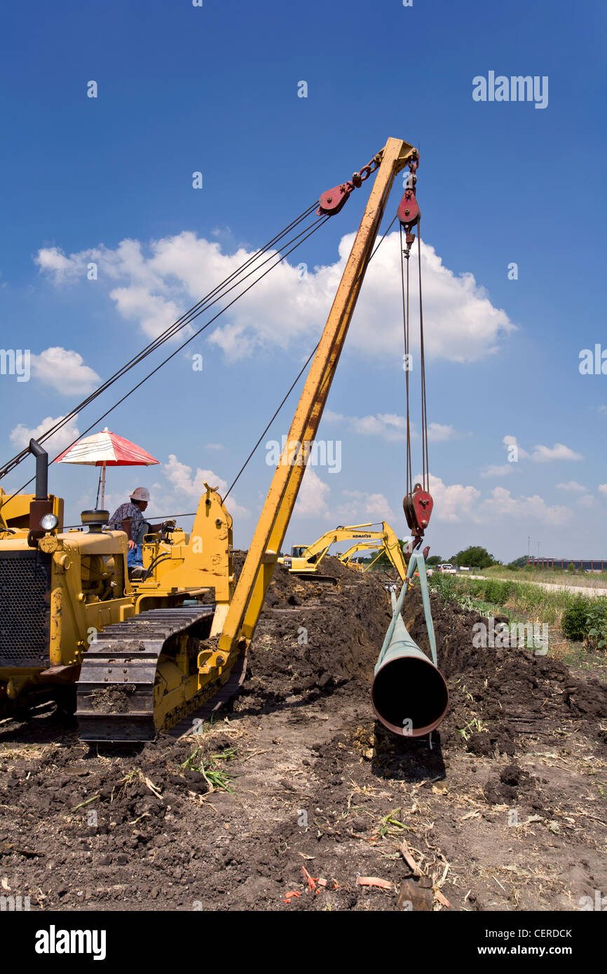 Crawler equipment sling a portion of the welded gas pipeline into the ground that will transport Barnette Shale - Stock Image