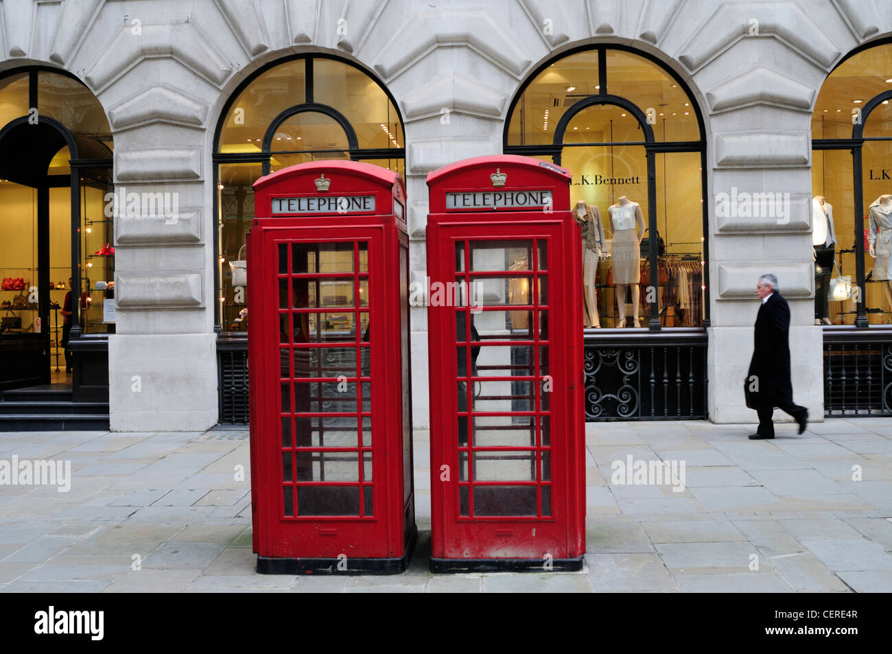 Red telephone boxes outside a L.K. Bennett clothes shop in the Royal Exchange. - Stock Image