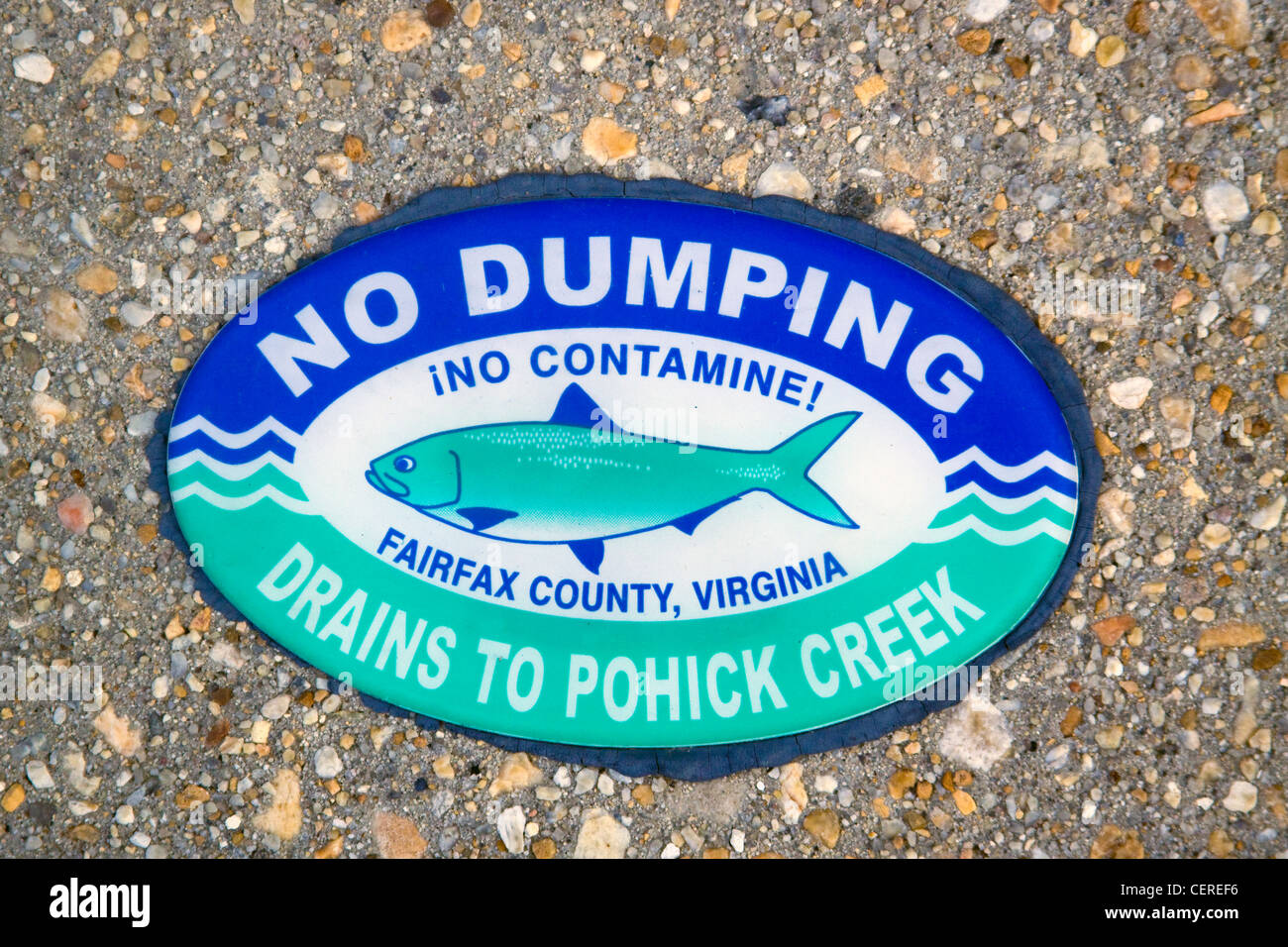 Fairfax County Virginia No Dumping Drains to Pohick Creek sign on top of a storm water drainage catch basin inlet - Stock Image