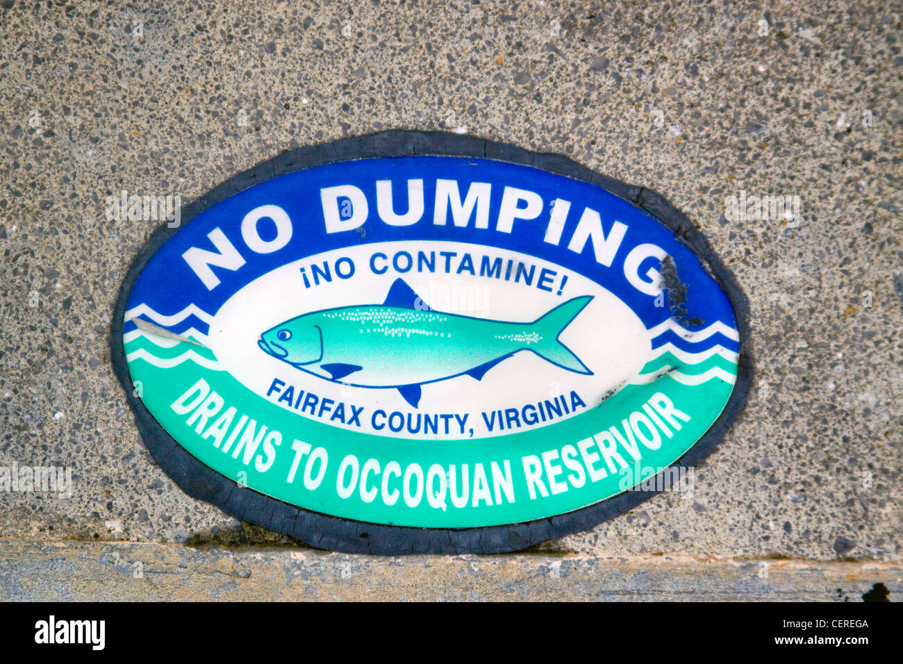 Fairfax County Virginia No Dumping Drains to Occoquan Reservor sign top of a storm water drainage catch basin inlet - Stock Image
