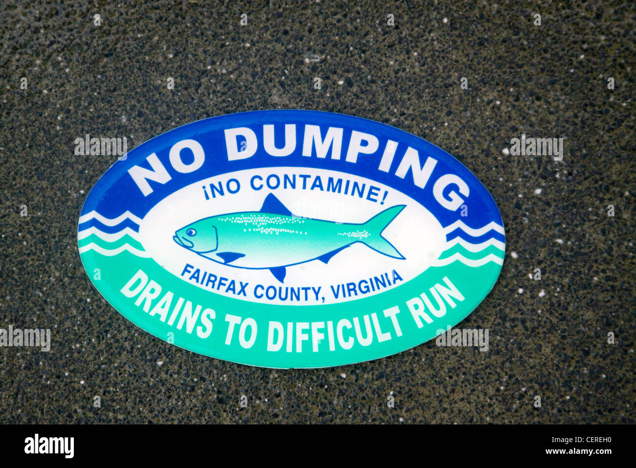 Fairfax County Virginia No Dumping Drains to Difficult Run sign on top of a storm water drainage catch basin inlet - Stock Image