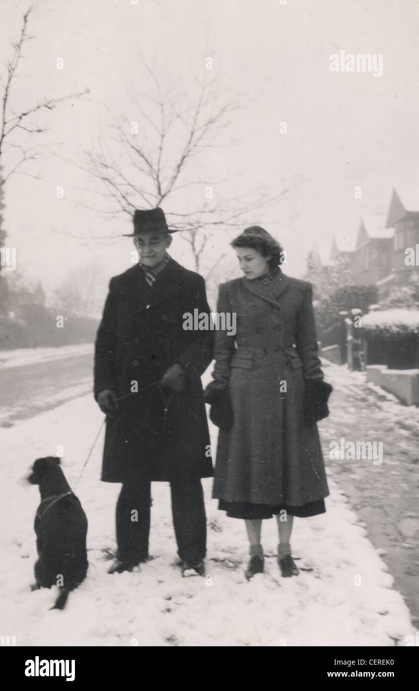 Couple in coats during snow, walking their dog (c1945) - Stock Image