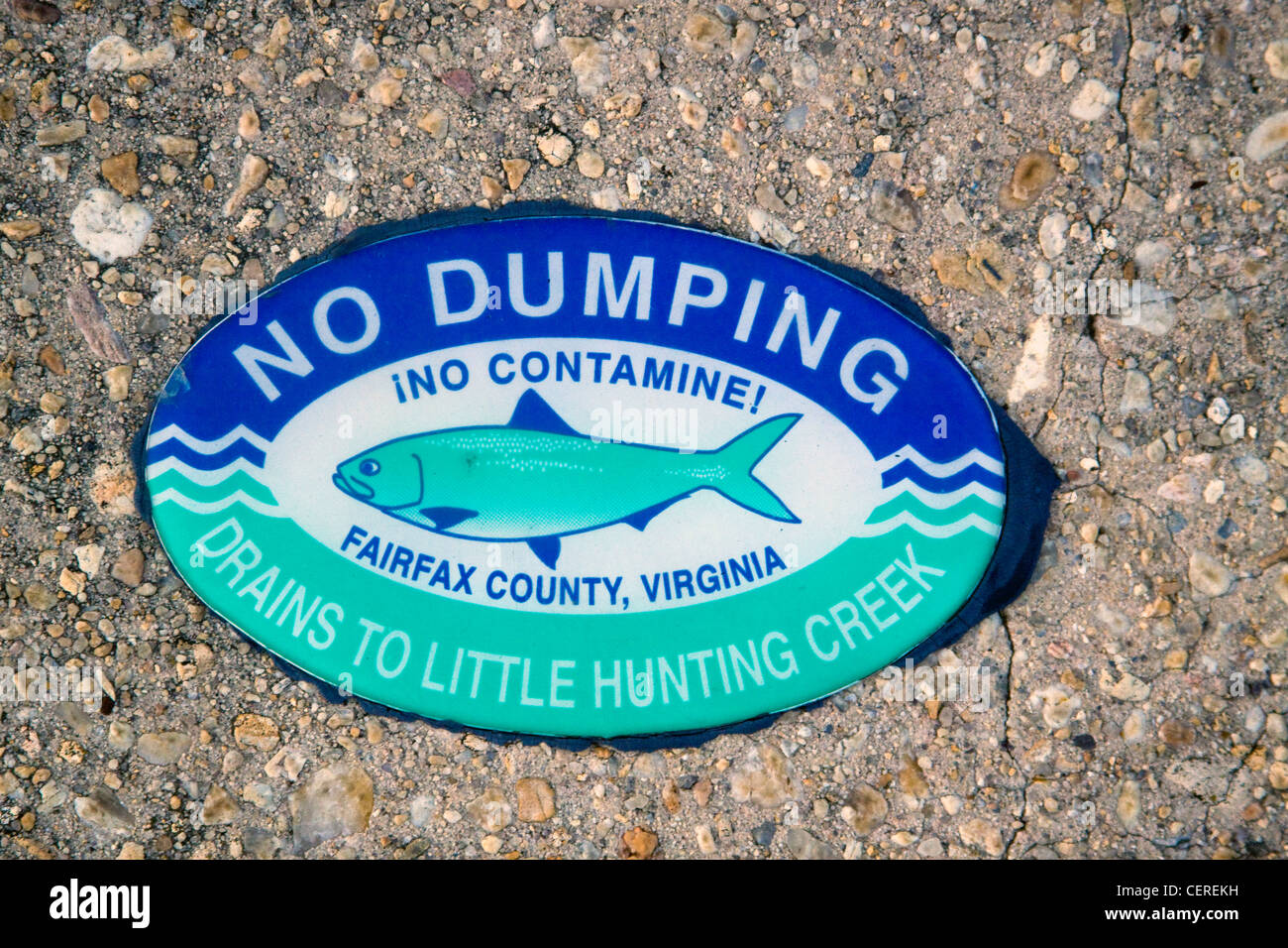 Fairfax County Virginia No Dumping Drains to Little Hunting Creek sign on top of a storm water drainage catch basin - Stock Image